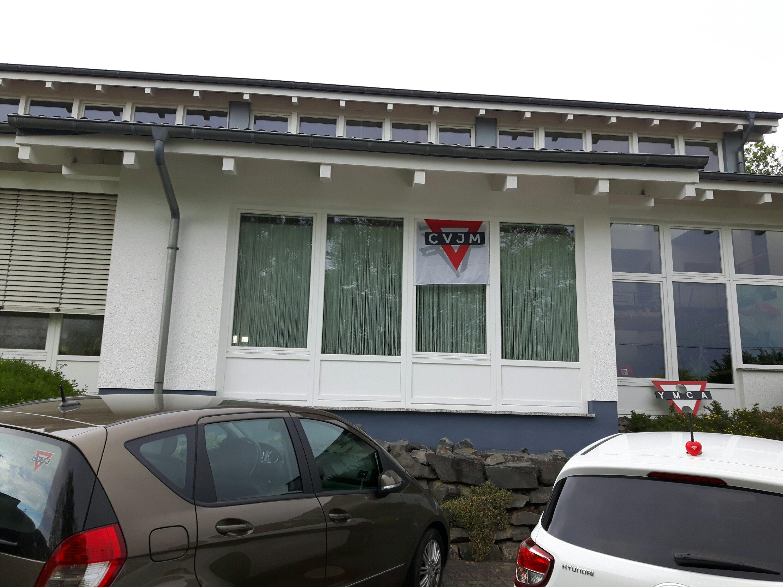 Außenbild der Kirche Alchen mit CVJM Flagge, an einem Auto auf dem Parkplatz ist ein CVJM-Aufkleber zu sehen.
